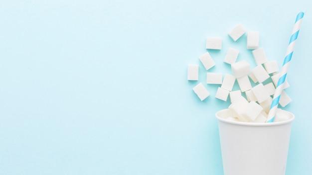 Вид сверху на чашку с кубиками сахара и соломинкой