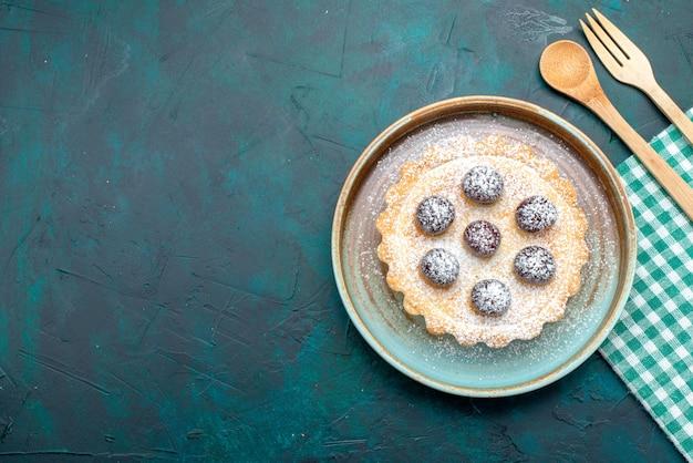 スプーンとフォークの横にさくらんぼと砂糖の粉とカップケーキの上面図