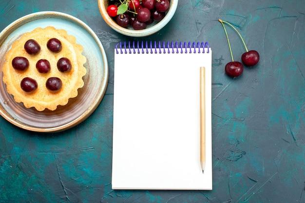 青のチェリーの次のノートブックとカップケーキの上面図、