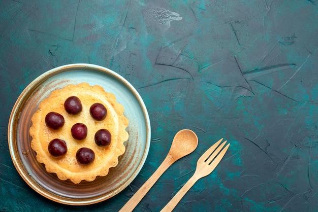 スプーンとフォークの横にあるおいしいチェリーとカップケーキの上面図