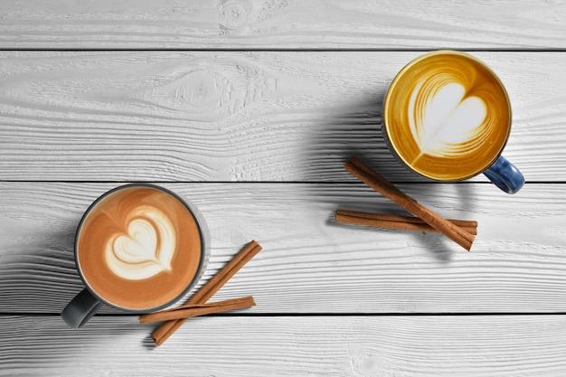 Вид сверху чашек кофе латте с корицей на белом фоне деревянные