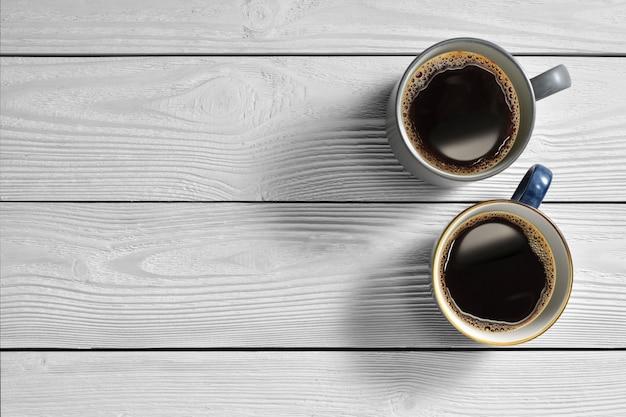 Вид сверху чашки кофе на белом фоне деревянные