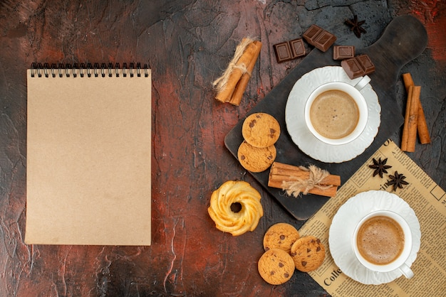木製のまな板と古い新聞クッキーシナモンライムチョコレートバーの暗い背景のノートブックの横にある一杯のコーヒーの上面図