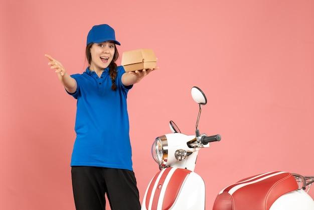 パステル ピーチ色の背景にケーキを保持しているオートバイの隣に立っている好奇心旺盛な宅配便の女の子のトップ ビュー