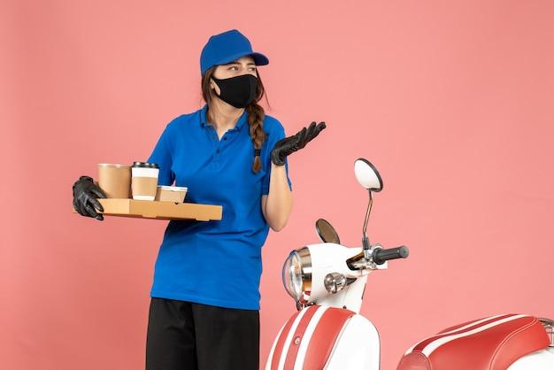 파스텔 복숭아 색 배경에 커피 작은 케이크를 들고 오토바이 옆에 서있는 의료 마스크 장갑을 끼고 호기심 택배 소녀의 상위 뷰