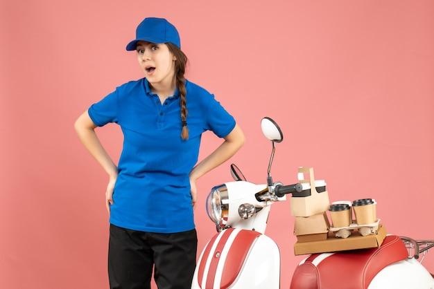 パステル ピーチ色の背景にコーヒーと小さなケーキを乗せたバイクの隣に立っている好奇心旺盛な宅配便の女性のトップ ビュー