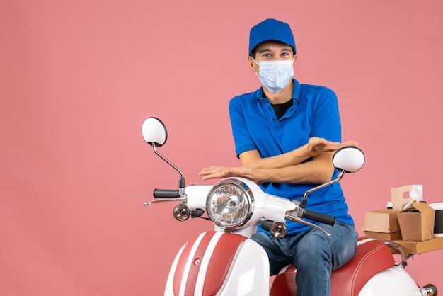 パステル調の桃の背景にスクーターに座っている帽子をかぶった医療マスクの好奇心旺盛な宅配便のトップビュー