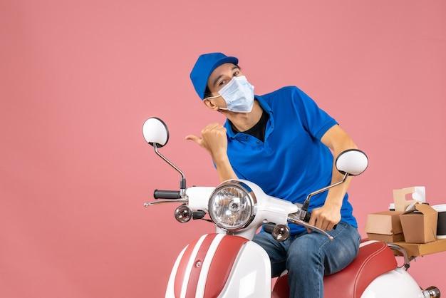 パステル調の桃の背景に何かを指すスクーターに座っている帽子をかぶった医療マスクを着た好奇心旺盛な宅配便のトップビュー