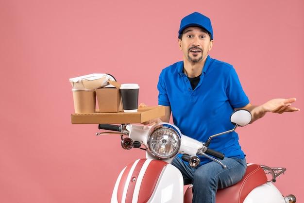 パステル調の桃の背景にスクーターに座っている帽子をかぶった好奇心旺盛な宅配便のトップビュー