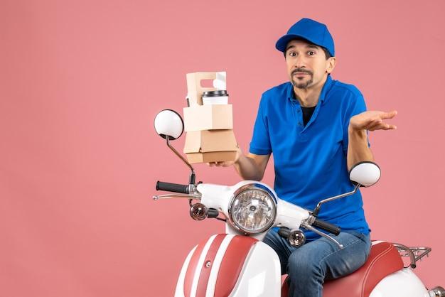 파스텔 복숭아 배경에 주문을 보여주는 스쿠터에 앉아 모자를 쓰고 호기심 택배 남자의 상위 뷰