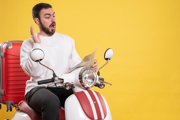 孤立した黄色の背景に混乱を感じて地図を見て、スーツケースを持ってオートバイに座っている好奇心旺盛な男のトップ ビュー