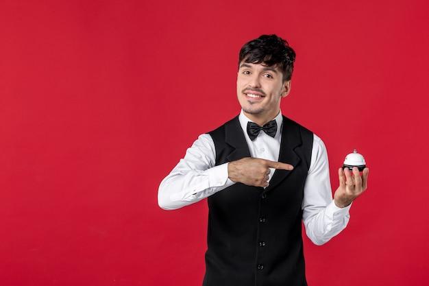 ポインティングリングベルを保持している蝶ネクタイと制服を着た好奇心旺盛な男のウェイターの上面図。