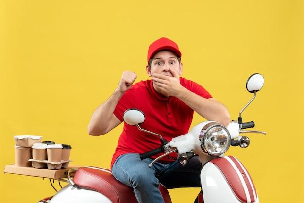 Вид сверху любопытного молодого человека в красной блузке и шляпе, доставляющего заказ, указывая на желтый фон