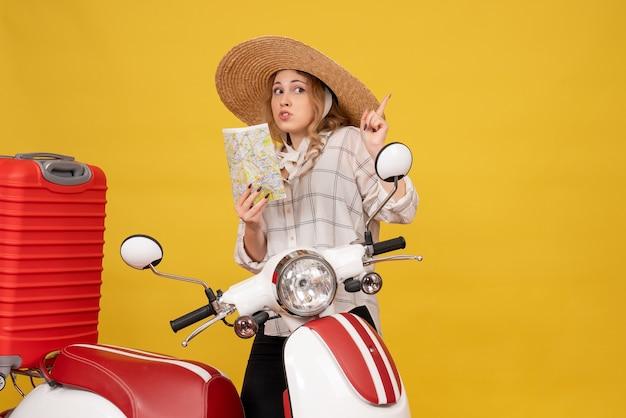 バイクに座って地図を上向きに保持している彼女の荷物を収集する帽子をかぶって好奇心旺盛な若い女性の上面図