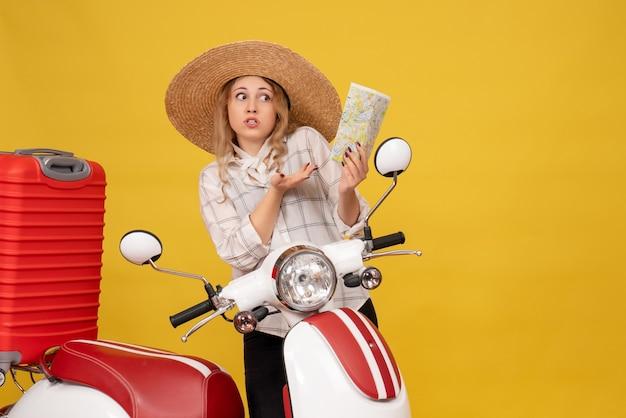 バイクに座って地図を保持している彼女の荷物を収集する帽子をかぶって好奇心旺盛な若い女性の上面図