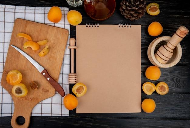 Вид сверху нарезанных и нарезанных абрикосов с ножом и блокнотом с шишкой на деревянном фоне