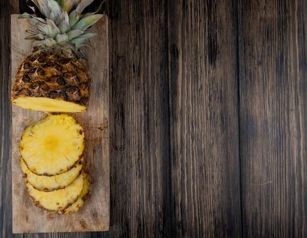 左側にあるまな板の上のカットとスライスしたパイナップルとコピースペースを持つ木製の背景の平面図