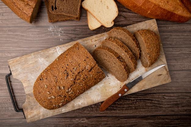 木製の背景にまな板の上のカットとスライスしたサンドイッチパンとナイフのトップビュー
