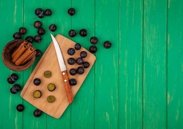 まな板の上のナイフとコピースペースと緑の背景にボウルにシナモンとカットと全体のスローベリーのトップビュー