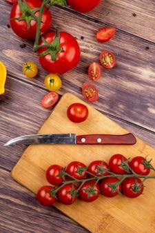 木のまな板の上のナイフでカットと全体のトマトのトップビュー