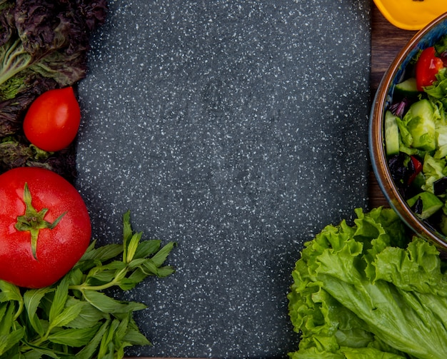 Вид сверху нарезанных и целых овощей как томатный базилик мята огуречный салат с разделочной доской в качестве поверхности