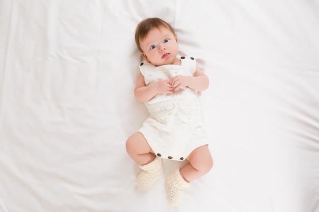 카메라를 보고 침실에서 흰색 몸을 입고 귀여운 사랑스러운 아기 소녀의 상위 뷰