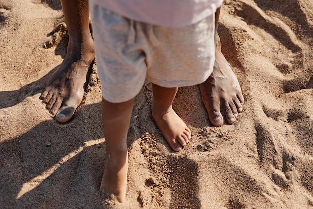 ビーチのコピースペースでお父さんと散歩を楽しみながら最初の一歩を踏み出すかわいい男の子の上面図