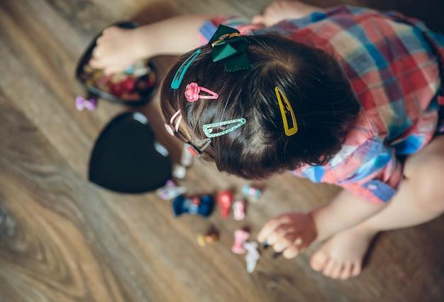 自宅の木の床に座って遊んでいるたくさんのヘアクリップとかわいい女の赤ちゃんの頭の上面図。頭に選択的に焦点を当てます。