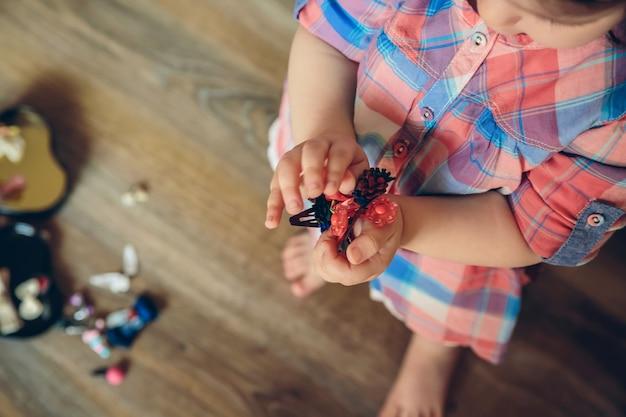 自宅の木の床の上で彼女の手でたくさんのヘアクリップで遊んでいるかわいい女の赤ちゃんの上面図。ヘアクリップに選択的に焦点を当てます。