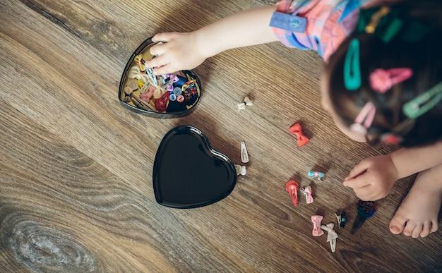 집에서 나무 바닥에 앉아 머리 클립 컬렉션을 가지고 노는 귀여운 아기 소녀의 상위 뷰
