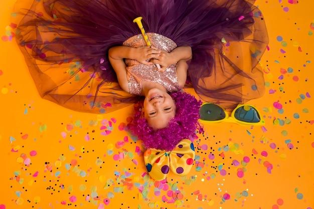 Вид сверху симпатичной девушки с клоунским париком и конфетти