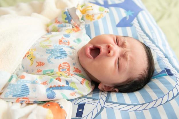 ベッドで寝る前にあくびをしているかわいい小さなアジアの赤ちゃんの上面図