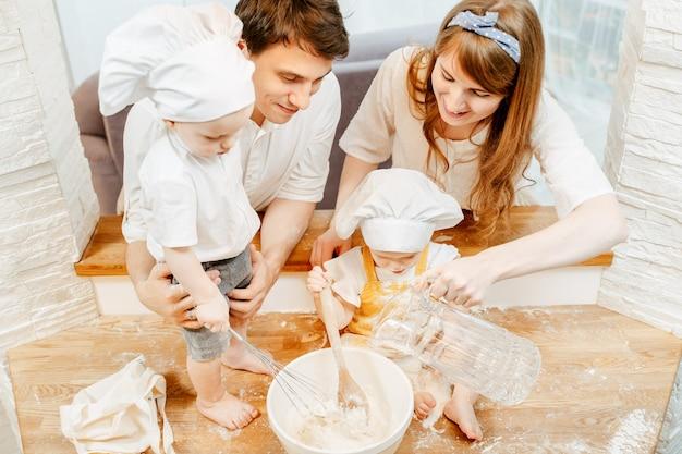かわいいポジティブな両親のお母さんとお父さんと子供たちの平面図は、居心地の良いキッチンでフリッター生地をこねます。共同料理と家族の伝統の概念
