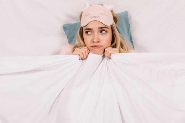 담요 아래 누워 귀여운 젊은 여자의 상위 뷰