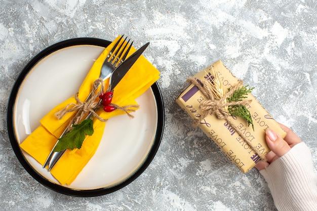 Вид сверху на набор столовых приборов для еды на белой тарелке и рука, держащая красивый упакованный подарок на поверхности льда