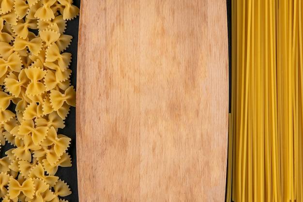Вид сверху на разделочную доску с сырыми макаронами и спагетти на черной поверхности