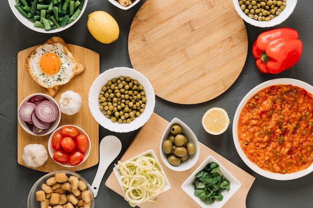 Вид сверху разделочных досок с жареным яйцом и оливками