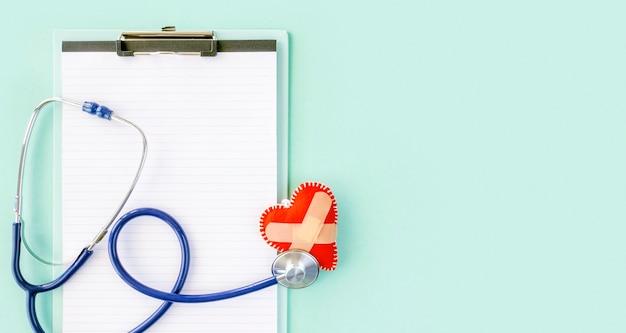 聴診器とメモ帳で破損したハートのトップビュー