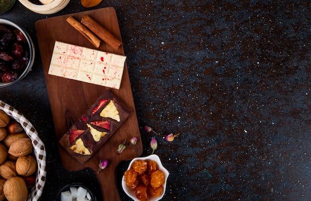 Вид сверху темного и белого шоколада с палочками корицы на деревянной доске и с сухофруктами и грецкими орехами на черном с копией пространства