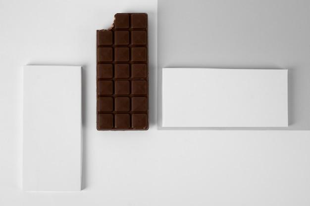 Вид сверху плитки темного шоколада с упаковкой