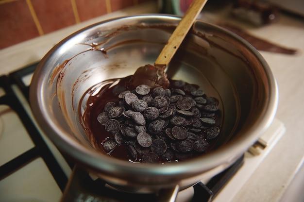 水浴のボウルにダークチョコレートの錠剤の上面図。世界のチョコレートデーを祝うための自家製チョコレート菓子の製造