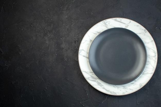 Вид сверху на пустые тарелки темного цвета и с белыми полосами двух размеров слева на черном фоне со свободным пространством