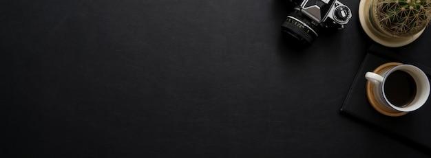 Вид сверху темной концепции офисный стол с камерой, украшениями и копией пространства