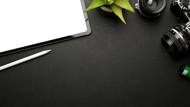Вид сверху темного творческого рабочего пространства с камерой цифрового планшета и копией пространства на черном столе