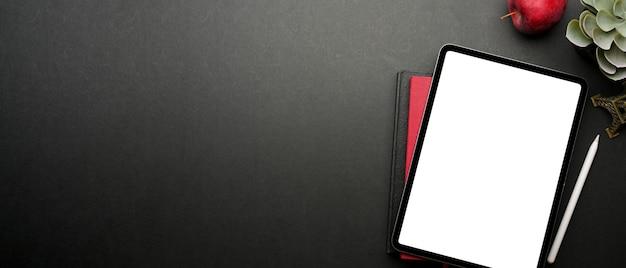 Вид сверху темного творческого рабочего пространства с цифровым планшетом, ноутбуком, яблоком, горшком и копией пространства, обтравочный контур
