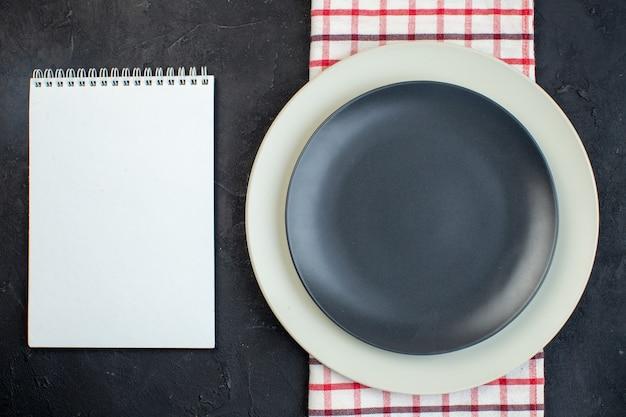 여유 공간이 있는 검정색 배경의 노트북 옆에 있는 빨간색 벗겨진 수건에 있는 짙은 회색 색상과 흰색 빈 접시의 상단 보기