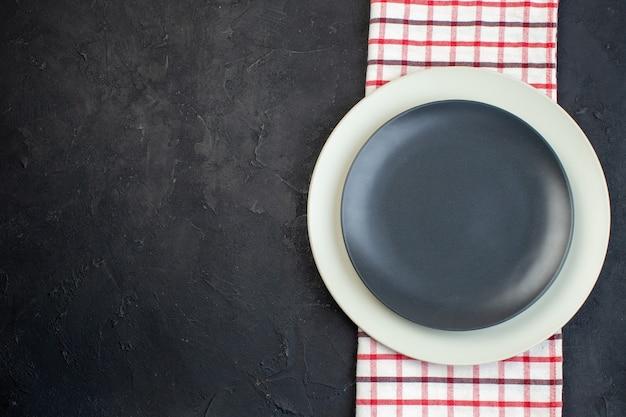 여유 공간이 있는 검정색 배경에 빨간색 벗겨진 수건에 짙은 회색 색상과 흰색 빈 접시의 상단 보기
