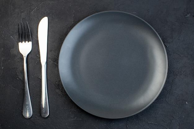 Вид сверху на пустую тарелку темно-серого цвета и набор столовых приборов из нержавеющей стали на черном фоне со свободным пространством