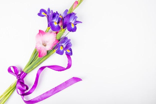 コピースペースと白い背景に分離された濃い紫とピンク色のアイリスとグラジオラスの花の上から見る