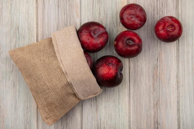 灰色の木製の壁に黄麻布の袋から落ちる濃い赤と甘いプルオットの上面図